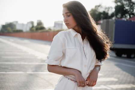 Young girl with long dark hair dressed in white shirt is standing in the street in the bright sunshine Banco de Imagens