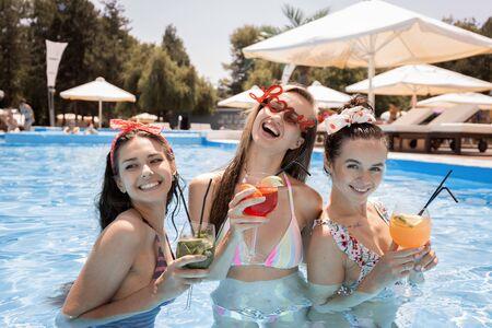 Les jeunes filles minces en maillot de bain se détendent et boivent des cocktails dans la piscine à côté du salon en plein air par une journée d'été ensoleillée Banque d'images