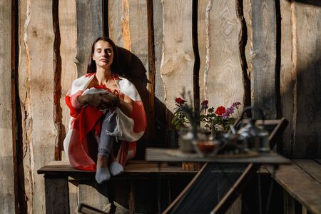 Young woman is sitting on a bench wrapped in a red and white plaid against a wooden wall next to a coffee table