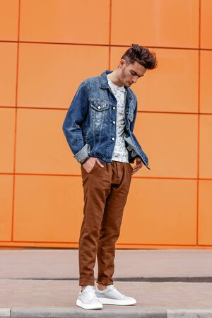 Young guy dressed in casual clothes brown trousers and jeans jacket poses in the street on the background of a orange wall