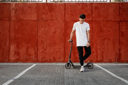 Young guy dressed in jeans and t-shirt stands with a scooter against a painted concrete wall on the summer day in the city.