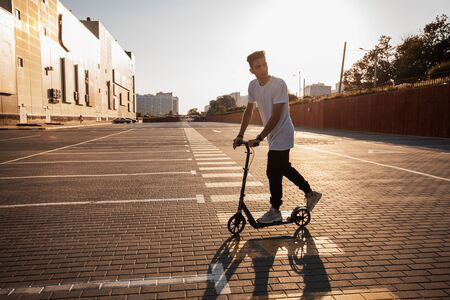 Young guy dressed in jeans and t-shirt is riding a scooter on the square paved with tiles near the building on the sunny day