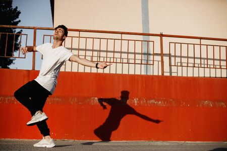 Young guy dressed in jeans and white t-shirt is dancing modern dance in the street against a painted concrete wall in the sunny day