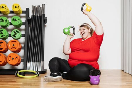 Fat and funny girl dressed in the sports wear is working out with dumbbells in the gym next to other sports equipment Stock Photo