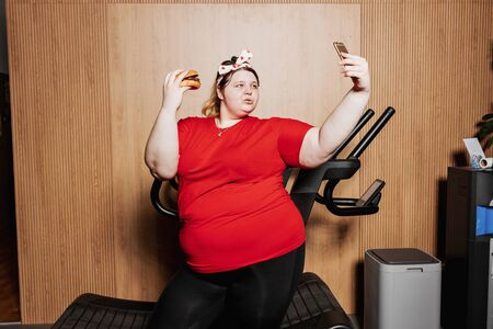 Fat and funny girl dressed in the sportswear and with a bandage on her head is making selfie standing with burger in her hand next to the treadmill Zdjęcie Seryjne
