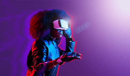 Mod curly dark haired girl dressed in black leather jacket and gloves uses the virtual reality glasses on her head in the dark studio with neon light