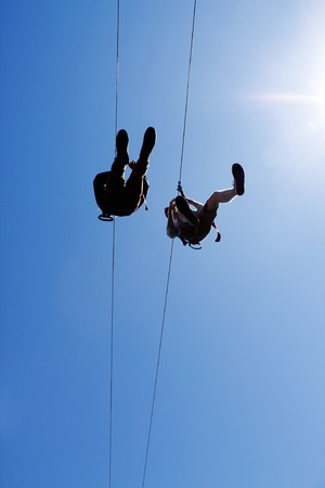 people zip lining through blue sky