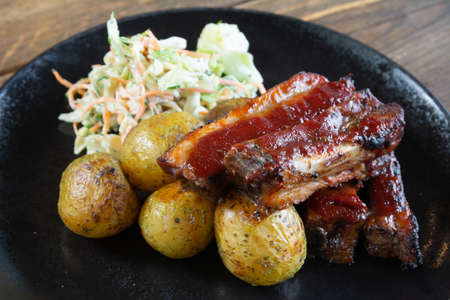 Meat potatoes and salad on black dishes.
