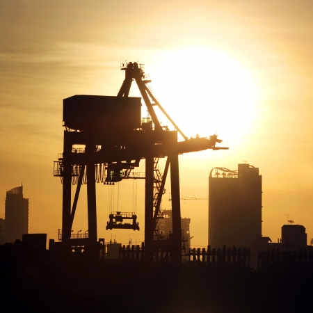 Silhouette of port warehouse with container cargo and crane bridge Stock Photo