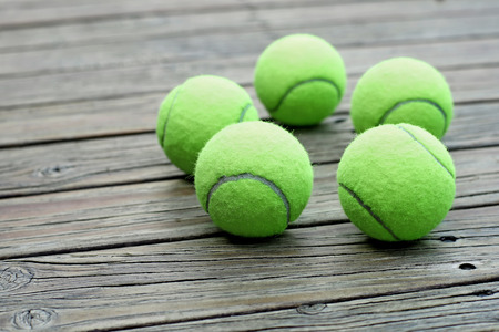 individual sport: pile of tennis ball  on wooden background Stock Photo