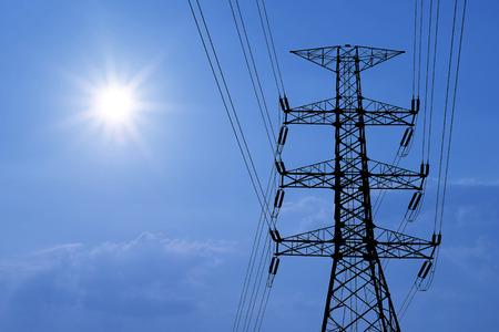 ingenieria elÉctrica: silueta de la torre eléctrica de alta tensión con un hermoso sol de fondo Foto de archivo