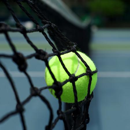 racket sport: tennis ball in the net