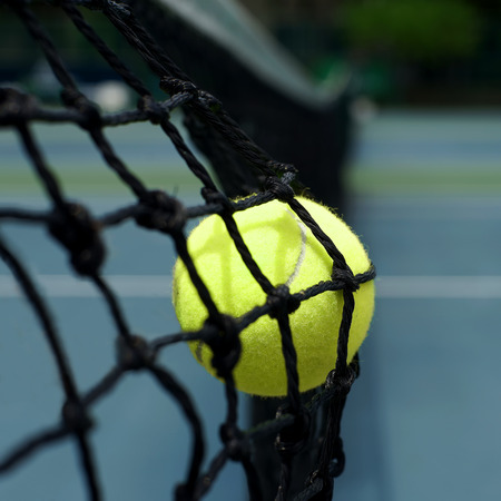 individual sport: exotic yellow color tennis ball in the net