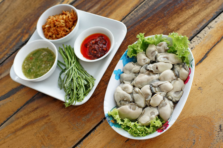 side dishes: fresh oysters with side dishes on wooden desk