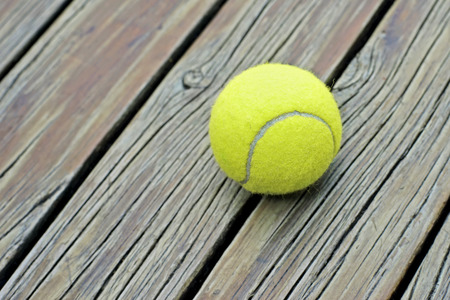 individual sport: yellow tennis ball  on wooden background