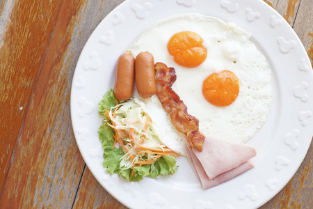 breakfast meal with ham sausage bacon egg and salad on wooden background