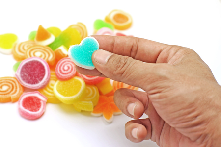 sweetmeats: human hand pick up jelly sweet candy isolated on white background