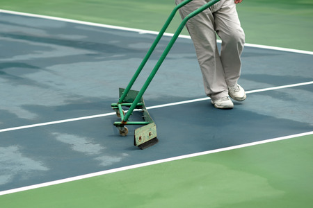cleaning crew: cleaning crew drying tennis court after rain