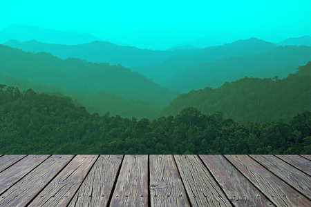 wooden floor with misty mountain hills landscape, layers of mountains with fog background Reklamní fotografie