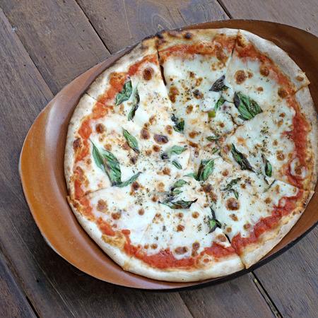 margherita: hot homemade margherita pizza on wooden background