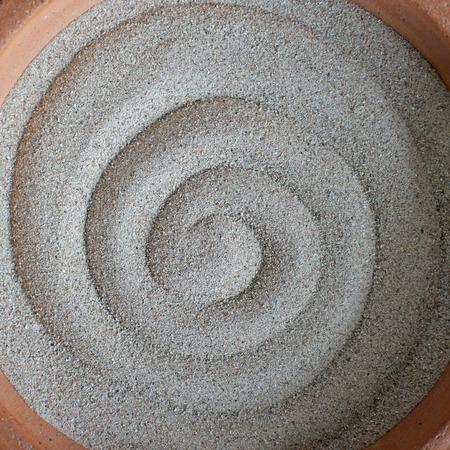 ashtray: a empty sand ashtray with circle pattern