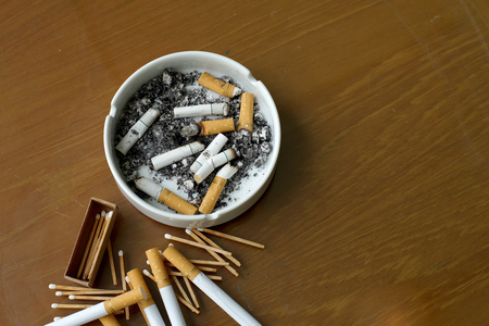 matchstick: smoked cigarettes in white ashtray and matchstick on wooden table Stock Photo