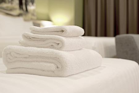 witte handdoeken opgerold en opgestapeld op bed Stockfoto