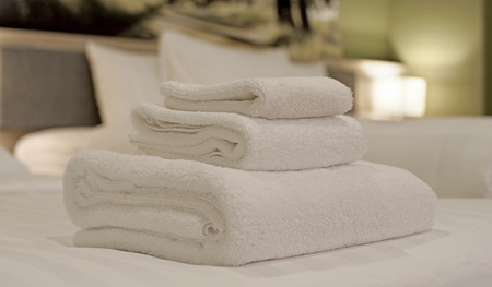 white towels: white towels rolled and piled on bed Stock Photo