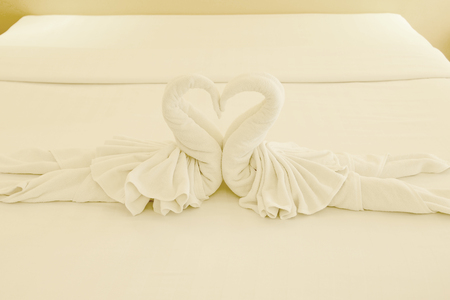 white towels: swans shaped of towel on the bed