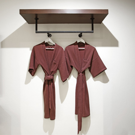 housecoat: two off brown bathrobes hanging on rack