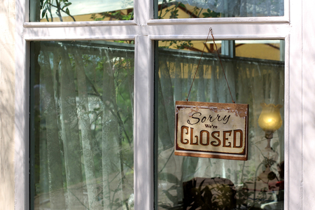 vintage closed sign hanging in front of shop window