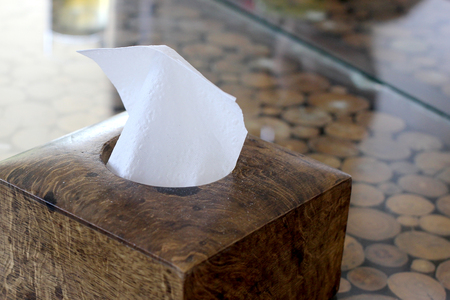 tissue paper in wooden box holder on table