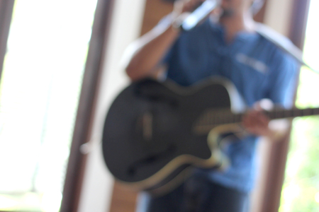 blurry photo of musician playing guitar with hand holding microphone Stock Photo