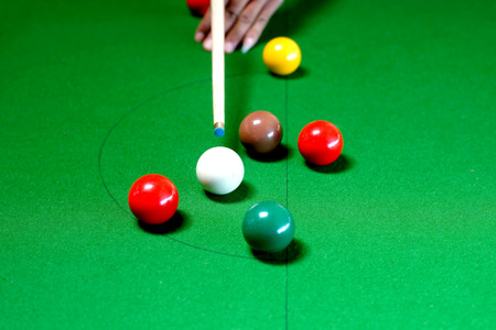 snooker game situation with the snooker player being ready to hit the white ball