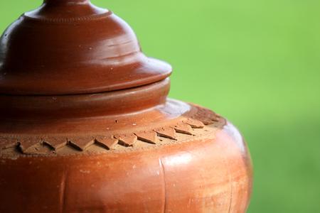 背景をぼかした写真のふた付きの手作り土鍋 写真素材