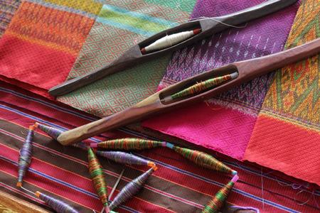colorful bobbins and wooden bobbin on silk fabric, traditional weaving of Thai silk Standard-Bild - 98078126