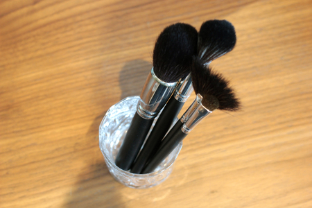 closeup of variety brushes for makeup in glass