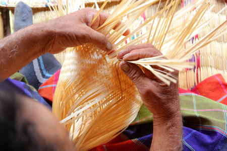 The villagers took bamboo stripes to weaving basket 免版税图像
