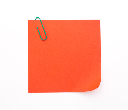 red sheet: red sheet of paper with green paper clip on a white background Stock Photo