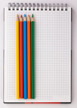 hoja en blanco: cuaderno y lápices de colores sobre un fondo blanco