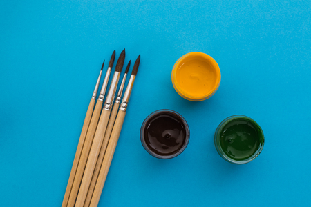 gouache: gouache and brushes on a blue background Stock Photo