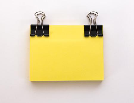 hoja en blanco: pila de hojas de papel amarillo con el clip de papel negro sobre un fondo blanco