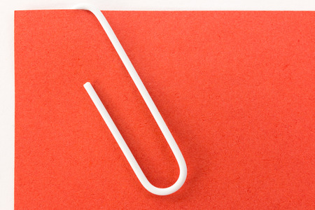 red sheet: white paper clip on a red sheet of paper macro Stock Photo
