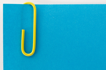 yellow paper clip on a blue sheet of paper macro