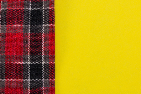 red plaid: red plaid fabric on yellow background closeup