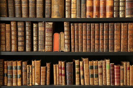 Old books on wooden shelf Imagens
