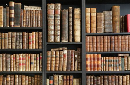 Antique books on wooden shelf in a library.