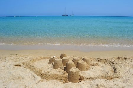 A sand castle on a sunny beach and calm clear sea water  Shot taken in Sardinia, Italy  photo