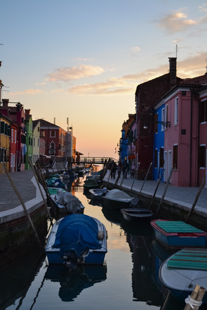 Sunset in the venetian lagoon;   Colorful houses in Burano a pictoresque  fishing village, near Venice  Venice, Italy - February 25, 2013