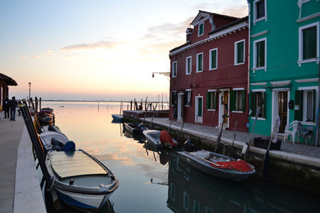 pictoresque: Sunset in the venetian lagoon;   Colorful houses in Burano a pictoresque  fishing village, near Venice  Venice, Italy - February 25, 2013